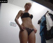 Lovely girl tries new clothes in the store changing room
